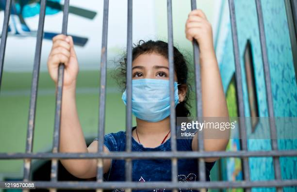 little girl wearing a face mask and peeking out from window - lockdown stock pictures, royalty-free photos & images