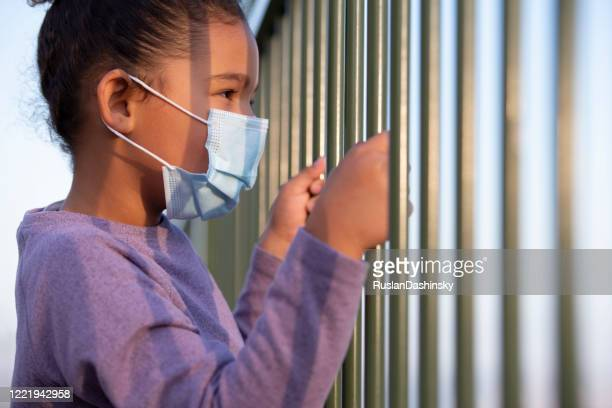 a little girl wearing a face mask, looking away through the fence rods. coronavirus pandemic concept. - child behind bars stock pictures, royalty-free photos & images