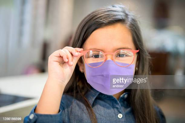 little girl wearing a facemask while trying glasses at the optician - eye care stock pictures, royalty-free photos & images