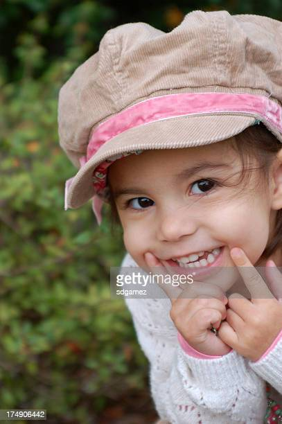 Little girl wearing a hat and being adorable