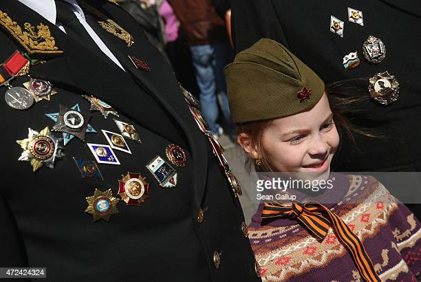 A little girl wearing a historical cap like those warn by Soviet Red Army soldiers during World War II poses with Russian military veterans near Red...