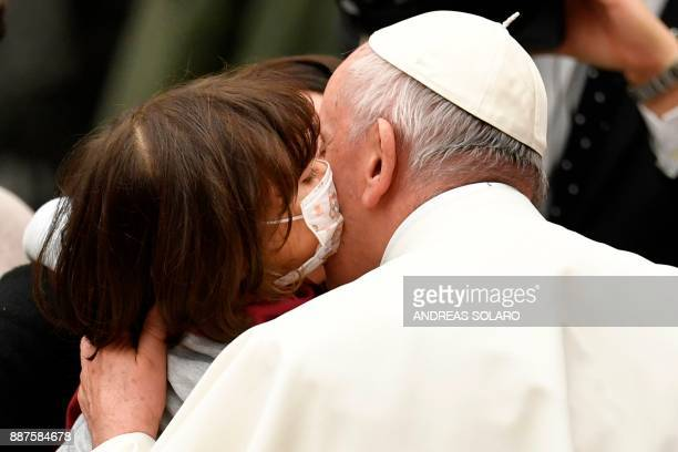 TOPSHOT A little girl wearing a mask kisses Pope Francis at the end of an audience to the Donor Delegations of the Christmas tree and the Nativity...