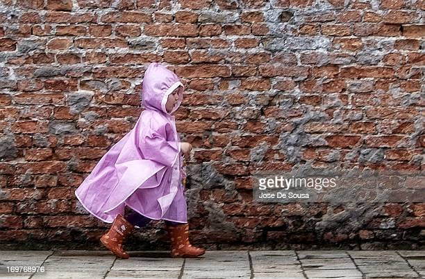 CONTENT] Little girl wearing a plastic purple raincoat with hood and rain boots walks confidently along textured brick wall in Venice Italy