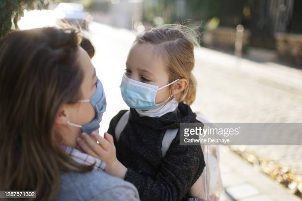 a little girl wearing a protective fac mask, embracing her mother in the street, before to go to school - france stock pictures, royalty-free photos & images