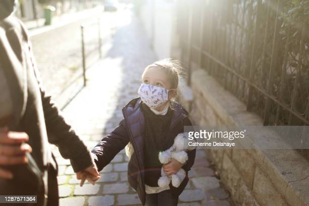 a little girl wearing a protective face mask, holding the hand of her mother in the street before to go to school - france stock pictures, royalty-free photos & images