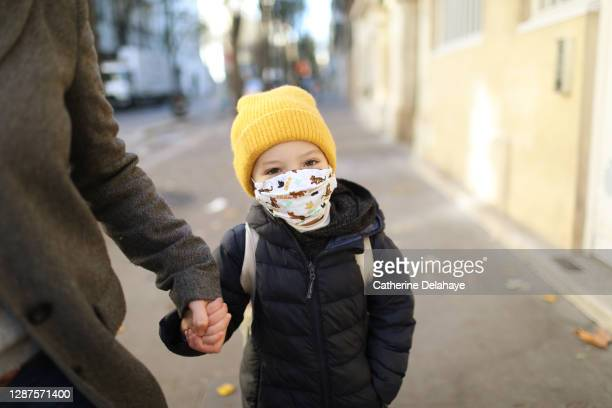 a little girl wearing a protective face mask, holding the hand of her mother in the street before to go to school - coronavirus winter stock pictures, royalty-free photos & images
