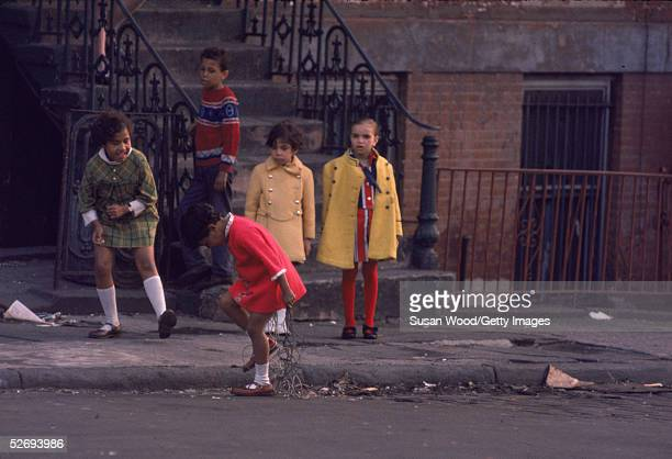 A little girl wearing a short pink dress white knee socks and brown mary janes tries to untangle herself from a bunch of wires as other children look...