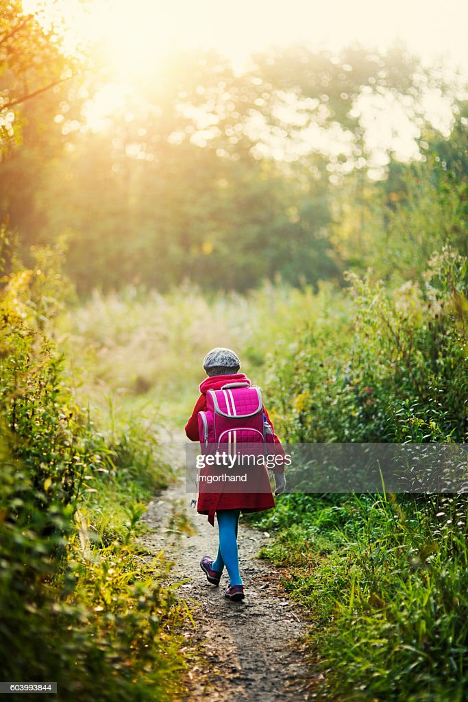 Little girl wearing big backpack walking to school : Stock Photo