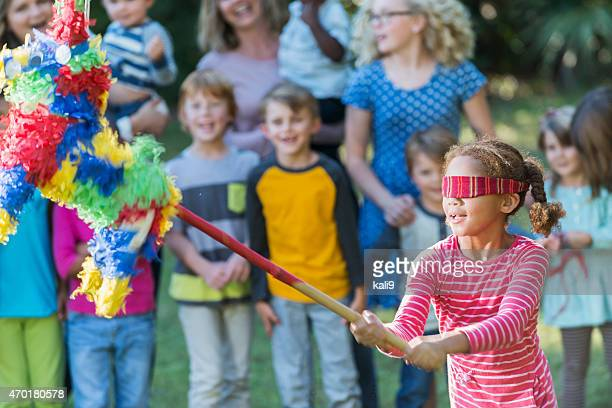 Little girl wearing blindfold hitting a pinata