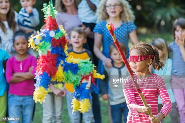 Little girl wearing blindfold hitting a pinata