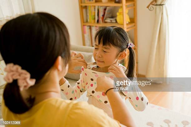 Little girl wearing clothes with mother