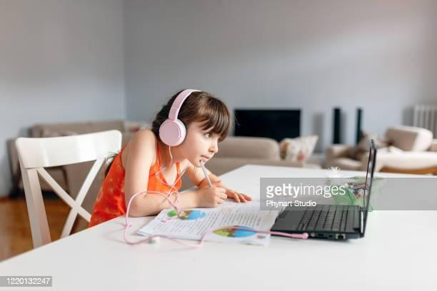 kleines mädchen trägt kopfhörer mit laptop vorbereitung hausaufgaben - 8 9 jahre stock-fotos und bilder