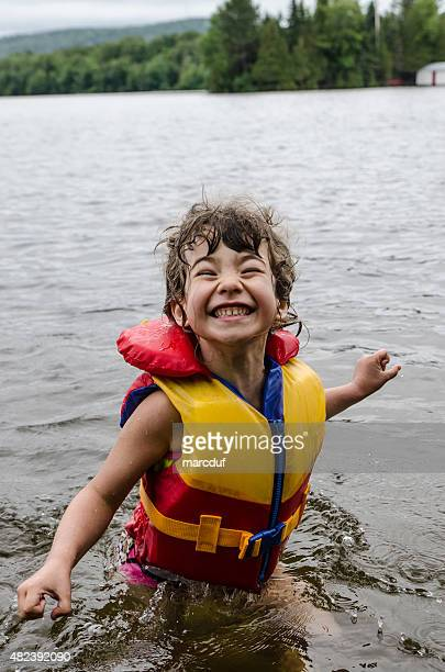 Little girl wearing life vest in lake and smiling