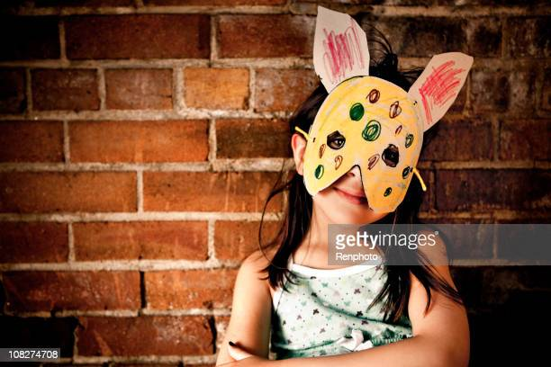 Little girl wearing paper bunny mask