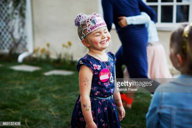 little girl wearing paper crown smiles in delight during birthday party - happybirthdaycrown stock pictures, royalty-free photos & images