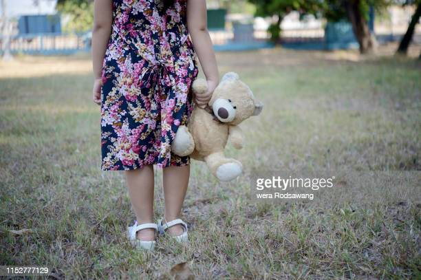 little girl wearing pink flower dress dragging the teddy bear walking in the park, domestic violence against children emotional concept - domestic violence stock pictures, royalty-free photos & images