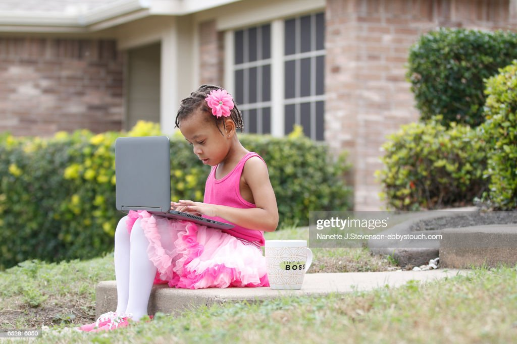 Little girl wearing pink Tutu with coffee and computer : Stock Photo