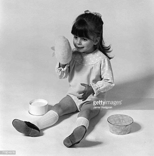 A little girl wearing polka dot pants and tshirt playing with a powder puff circa 1960