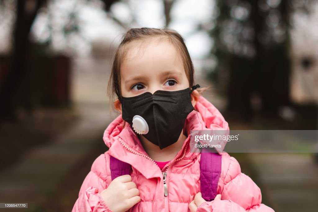 Little girl wearing pollution mask. : Stock Photo