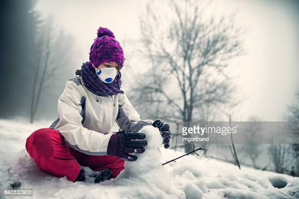 Little girl wearing pollution mask playing in snow