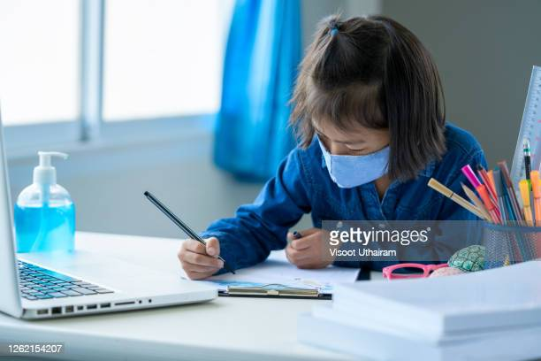 little girl wearing protective mask to protect against covid-19,asian children student online learning class study online at home. - distance learning stock pictures, royalty-free photos & images