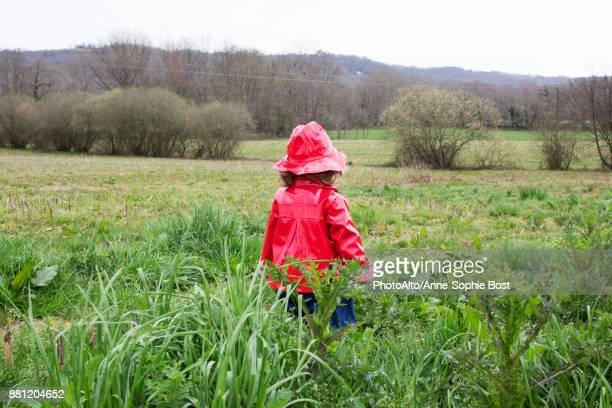 Little girl wearing rain gear playing in field