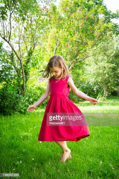 Little girl wearing red summer dress dancing on a meadow