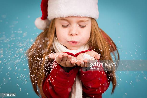 Little Girl Wearing Santa Hat and Blowing Handful of Snow
