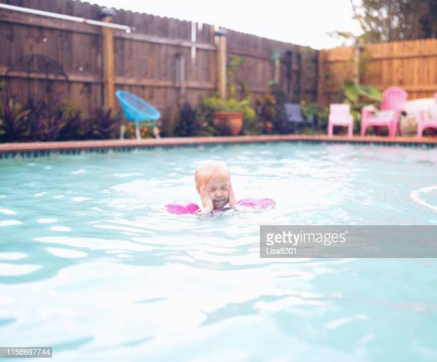 little girl wearing swimmers in a pool - bloodshot stock pictures, royalty-free photos & images