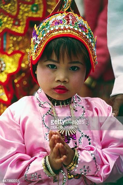 Little girl wearing traditional clothes during the Shinpyu Buddhist novitiation ceremony Mahamuni temple Mandalay Burma