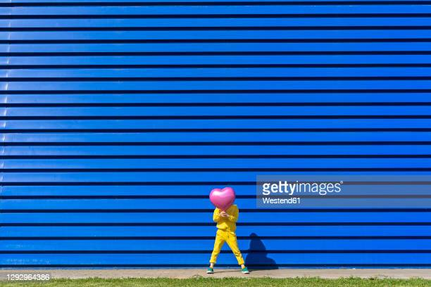 little girl wearing yellow tracksuit standing in front of blue background hiding behind pink balloon - obscured face stock pictures, royalty-free photos & images