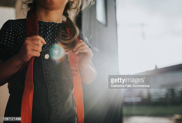 little girl wears a backpack in a sunny environment - focus is on her gripping the straps on her shoulders - human back stock pictures, royalty-free photos & images