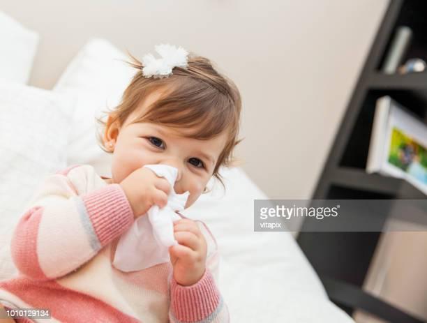 niña, limpiando su nariz con un pañuelo - resfriado y gripe fotografías e imágenes de stock