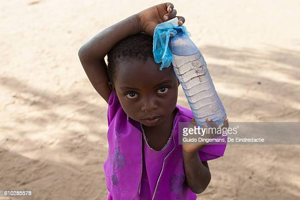 little girl with a bottle of water (malawi) - humanitarian aid stock pictures, royalty-free photos & images