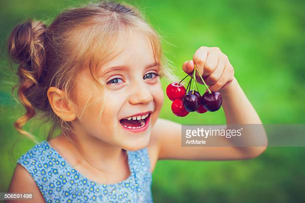 Little girl with a cherry
