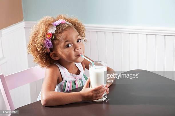 Kleines Mädchen mit einem Glas Milch