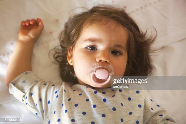Little girl with a pacifier in the bed