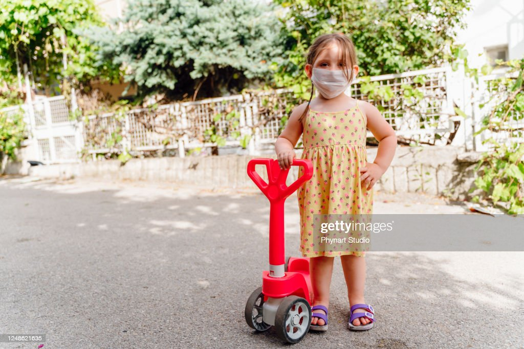 Little girl with a scooter and a medical mask : Stock Photo