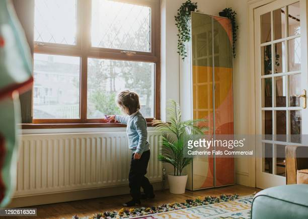 little girl with a small toy playing by a sunny window in a domestic room - home interior stock pictures, royalty-free photos & images