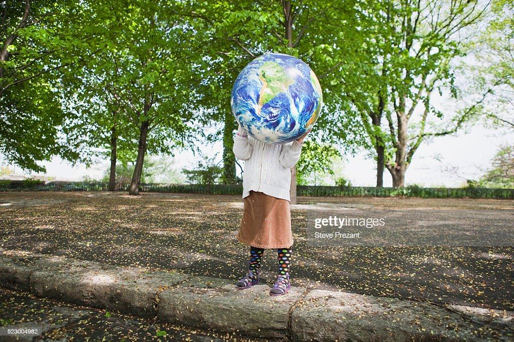 little girl with a world map beach ball stock photo