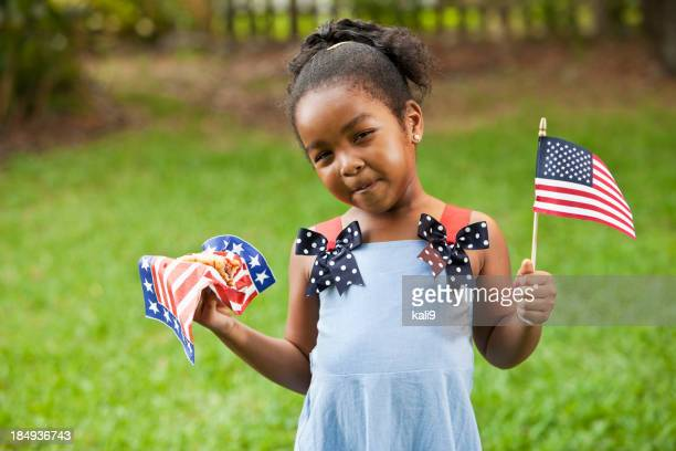 Little girl with American flag and hotdog