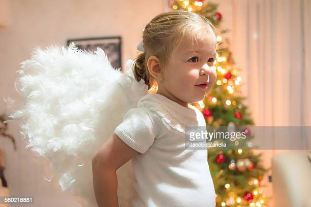 Little girl with angel wings by Christmas tree