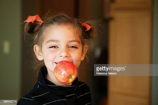 little girl with apple in her mouth - rebecca nelson stock pictures, royalty-free photos & images