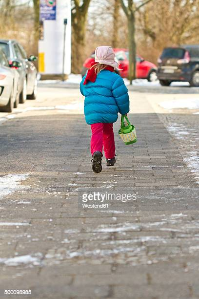 Little girl with bag on pavement