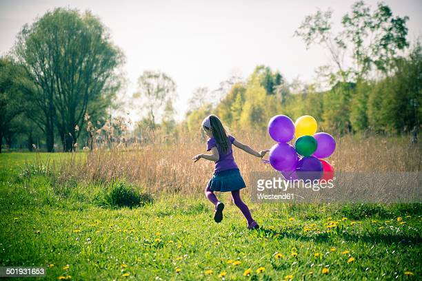 little girl with balloons running on a meadow - innocence stock pictures, royalty-free photos & images