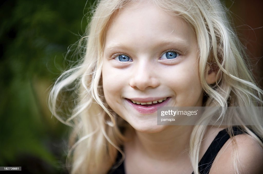 Little girl with big blue eyes and blonde hair : Stock Photo