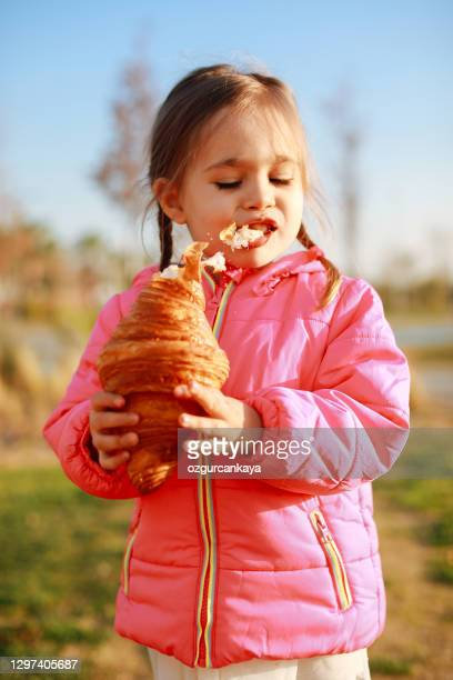 little girl with blond hair eating crispy croissant outdoors on street - french food stock pictures, royalty-free photos & images