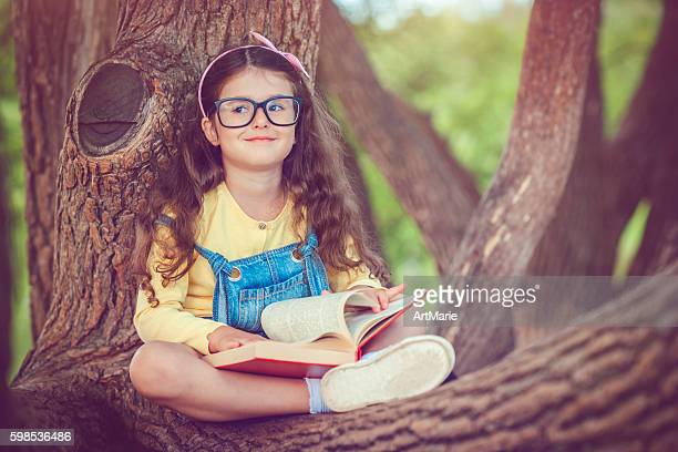 Little girl with book in autumn