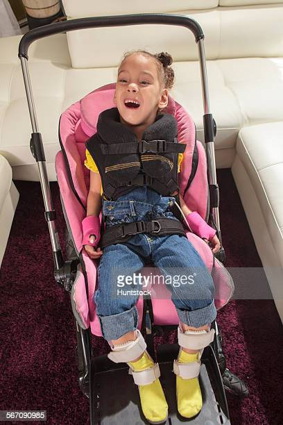 Little girl with Cerebral Palsy ready to go for a ride in a stroller