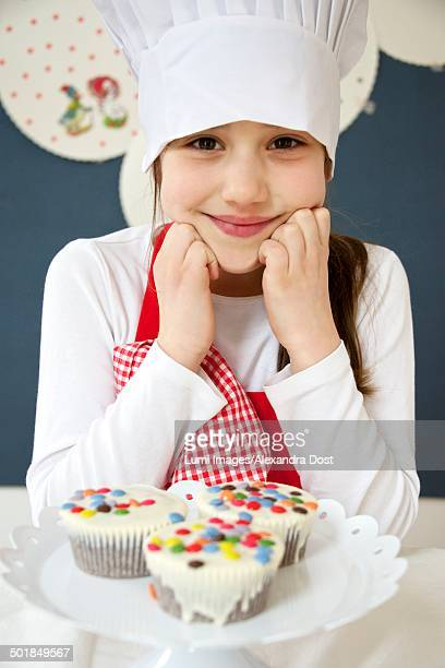 Little girl with chef's hat presenting muffins, Munich, Bavaria, Germany